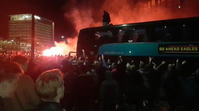 De spelersbus omringd door vele honderden fans.