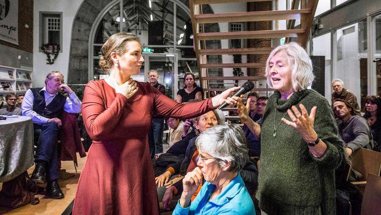Debat over de democratie in De Hallen. De gespreksleidster houdt de microfoon ferm in handen Beeld Dingena Mol