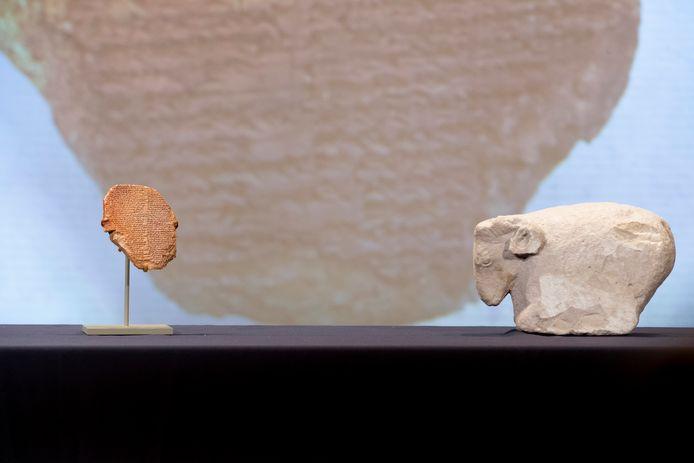 Lempeng tanah liat yang tertulis bagian dari Epik Gilgames, di sebelah patung domba jantan.