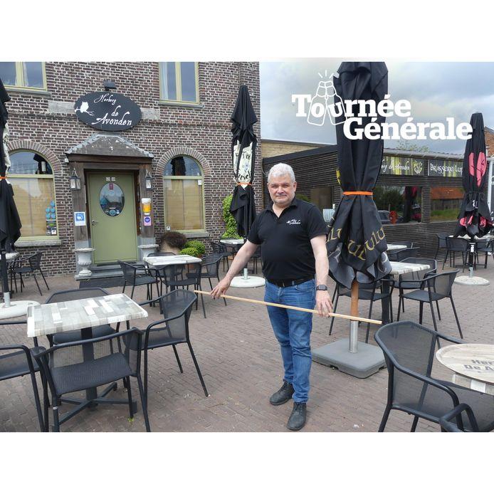 Piet Deolet meet de afstand tussen de tafels op zijn terras.