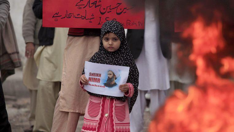 Een meisje met het portret van Nimr al-Nimr tijdens een demonstratie in Peshawar, Pakistan. Beeld reuters