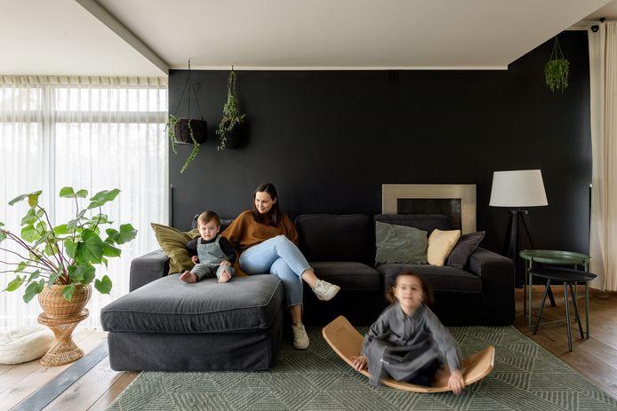 De zwarte muur bakent het salon enkel visueel af van de rest van de woonkamer.