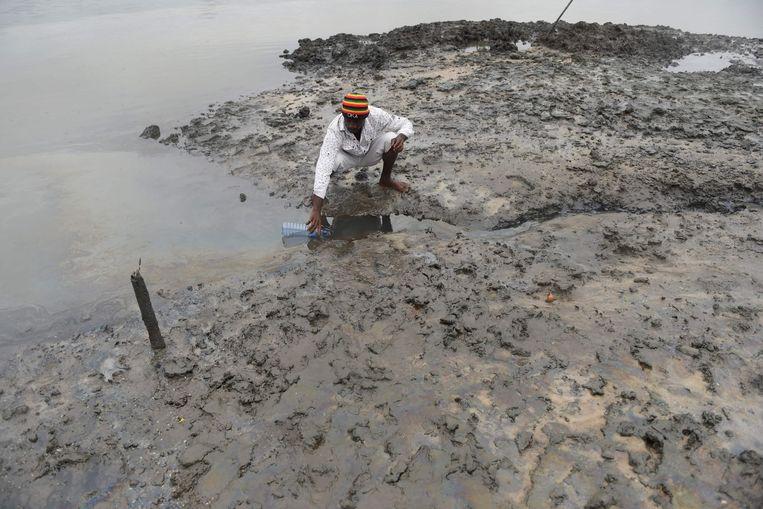 Een visser haalt water uit de vervuilde Bodo rivier in Bodo, in het Gokana district van Ogoniland, in het zuidoosten van Nigeria. Beeld AFP