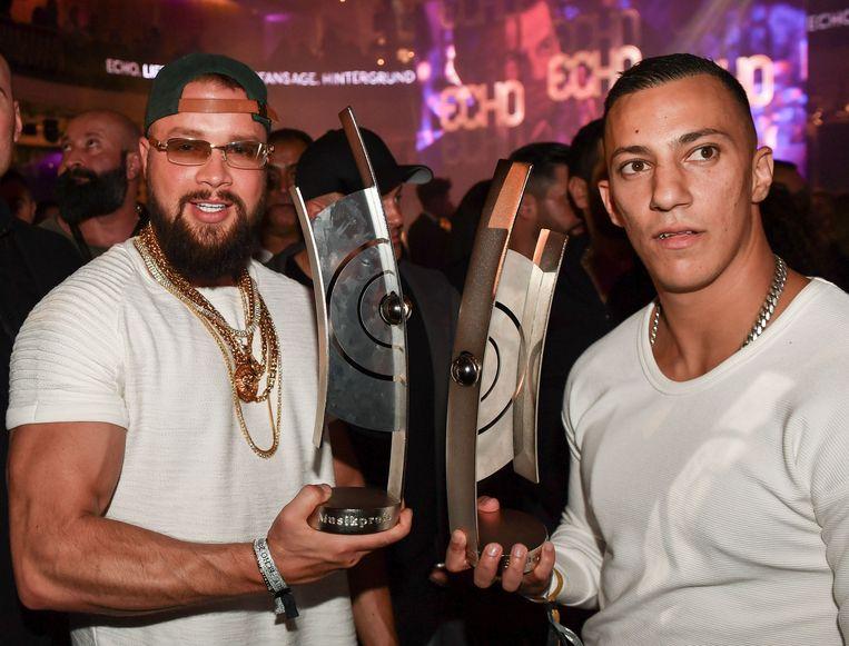 Kollegah en Farid Bang met hun Echo-award voor het album 'Jung, brutal, gutaussehend', waarop antisemitische lyrics te horen zijn, wat bij velen wrevel opwekt.  Beeld AFP