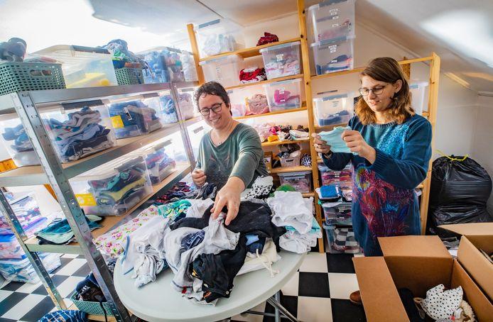 Suzanne van Schoonhoven (l) en Roos Nutma van Stichting BabyJump sorteren kleding in de inmiddels te kleine opslagruimte.