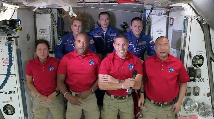 Dragon-crew Shannon Walker, Victor Glover, Mike Hopkins en Soichi Noguchi (vooraan, rode polo's) poserend voor een foto met ISS-crew Kate Rubins, Sergey Ryzhikov en Sergey Kud-Sverchkov.