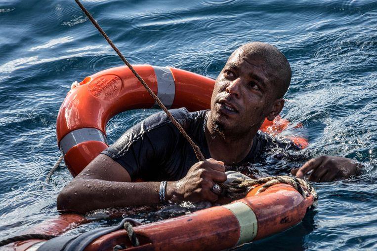 Een Libische migrant in de Middellandse Zee.  Beeld AFP