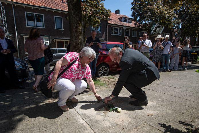 Maxim Krukziener en zijn zus leggen in de Schilderswijk een witte roos bij de gedenksteen voor hun familie. Maxim Krukziener: ,,Hier woonden dappere mensen, die hun leven riskeerden om anderen te redden. Dankzij die helden bleven mijn grootouders in leven en ben ik er nu.''
