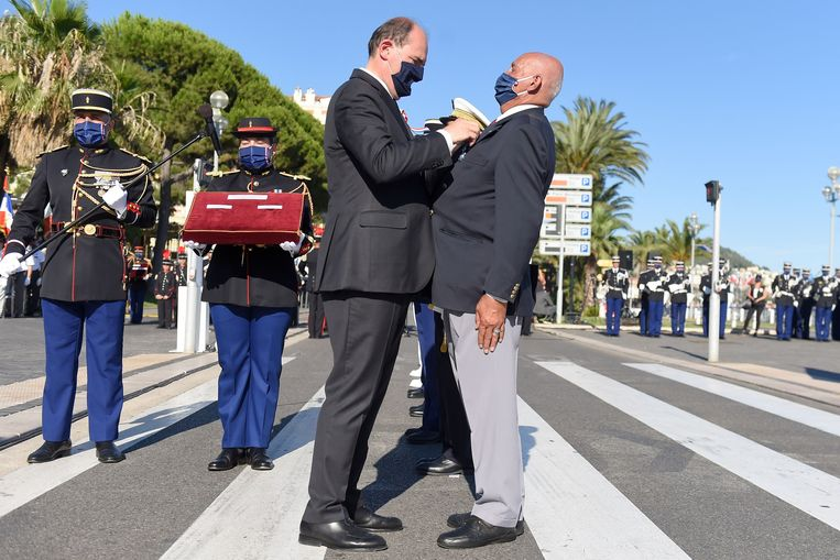 De Franse premier Jean Castex onderscheidt in Nice een veteraan op Quatorze Juilliet, afgelopen woensdag. Juist in deze badplaats heeft de nationale feestdag nog altijd een zwart randje, vanwege de terreuraanslag met een truck die hier vijf jaar geleden plaatsvond op de Promenade des Anglais. Daarbij kwamen 86 mensen om het leven.  Beeld AFP