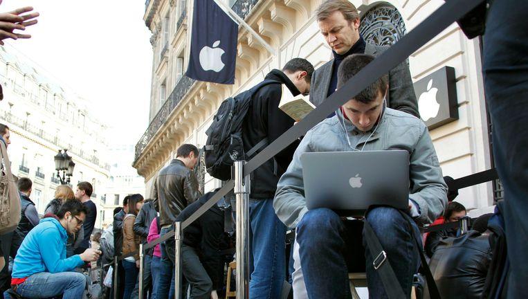Een lange rij klanten voor de Apple Store in Parijs. Foto Beeld reuters