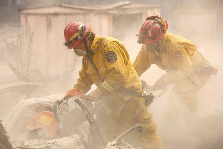 Brandweermannen gaan door de restanten van een huis in Paradise. Beeld REUTERS