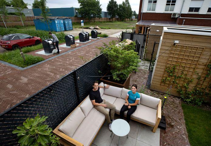 Erik Hurkmans en zijn vriendin Vera Zuidhof in hun tuin met daarnaast de kleine 'milieustraat' in nieuwbouwwijk Nuenen-West.