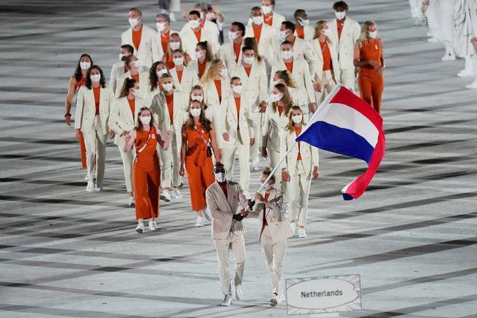 Brigitte Sleeking, rechts van de sporter met de lange donkere haren tussen de twee vrouwen in het rood, tijdens de openingsceremonie in het olympisch stadion van Tokio. FOTO AP