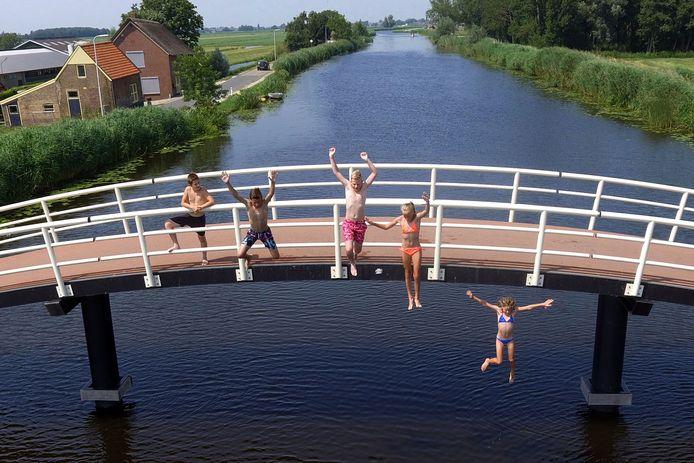 Jongeren springen in Brandwijk van een brug.