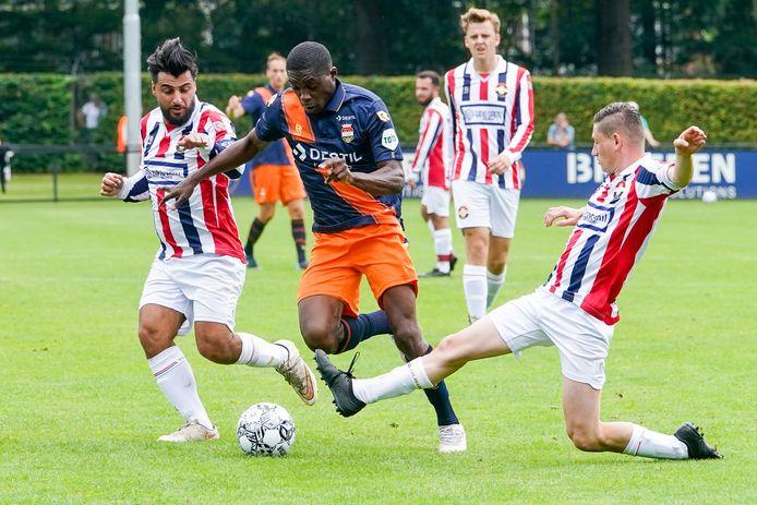 Derrick Köhn probeert de tackle van een speler van Willem II-amateurs te ontwijken.
