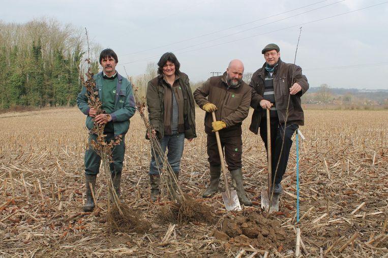 Schepen De Ridder (r.) en boswachter Wouter Huygens (tweede van rechts) planten de eerste bomen, met hulp van een ANB-team.
