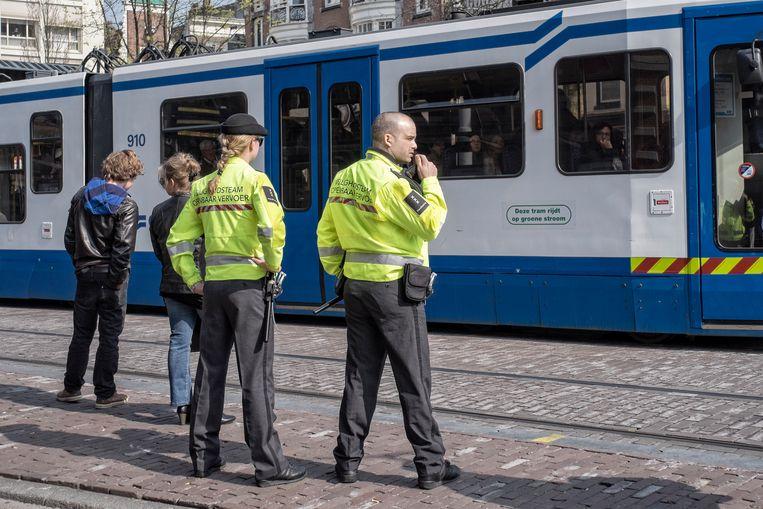 Twee leden van het Veiligheidsteam Openbaar Vervoer patrouilleren bij een tramhalte op het Leidseplein in Amsterdam. Mannen hebben in dezelfde functie vaak een net iets hoger salaris.   Beeld Patrick Post