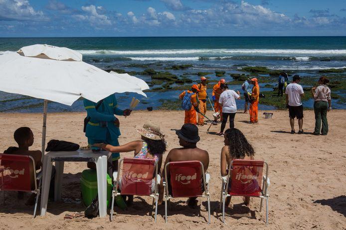 Tussen de strandgasten door maken gemeentewerkers en vrijwilligers het strand schoon in Lauro de Freitas in de staat Bahia in Brazilië.