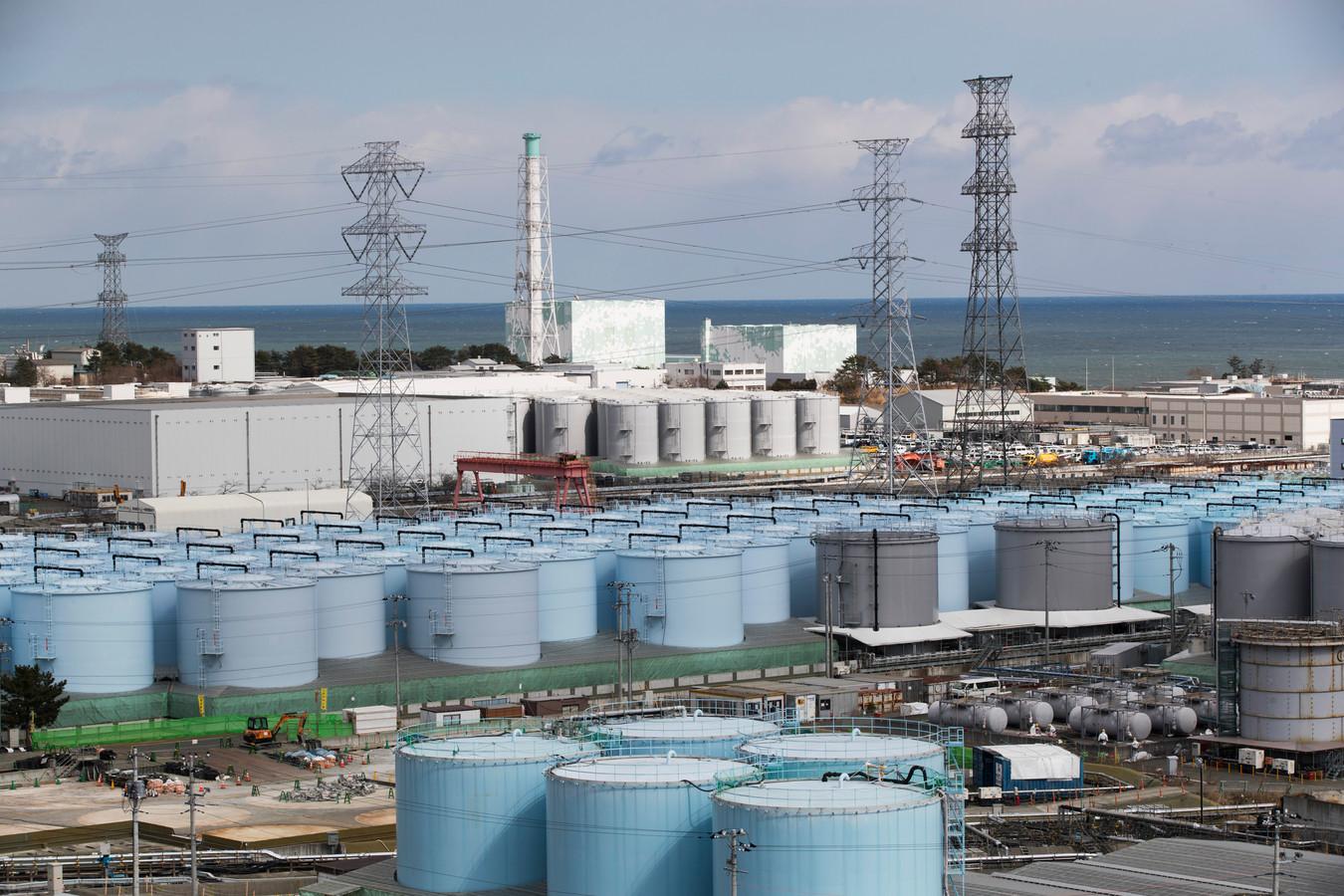 Sur cette photo d'archive du samedi 27 février 2021, les réacteurs nucléaires n°5, au centre gauche, et n°6 regardent des réservoirs stockant de l'eau traitée mais toujours radioactive, à la centrale nucléaire de Fukushima Daiichi dans la ville d'Okuma, préfecture de Fukushima, au nord-est du Japon.