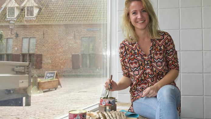Maartje Schoolderman prikt in pulled pork uit blik in de etalage van haar miniwinkel.