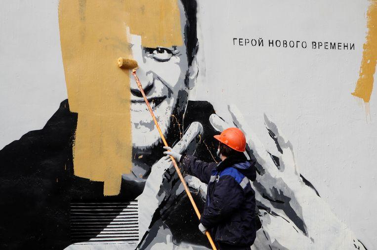In Sint-Petersburg wordt een muurschildering van oppositieleider Navaly weggewerkt. Beeld REUTERS