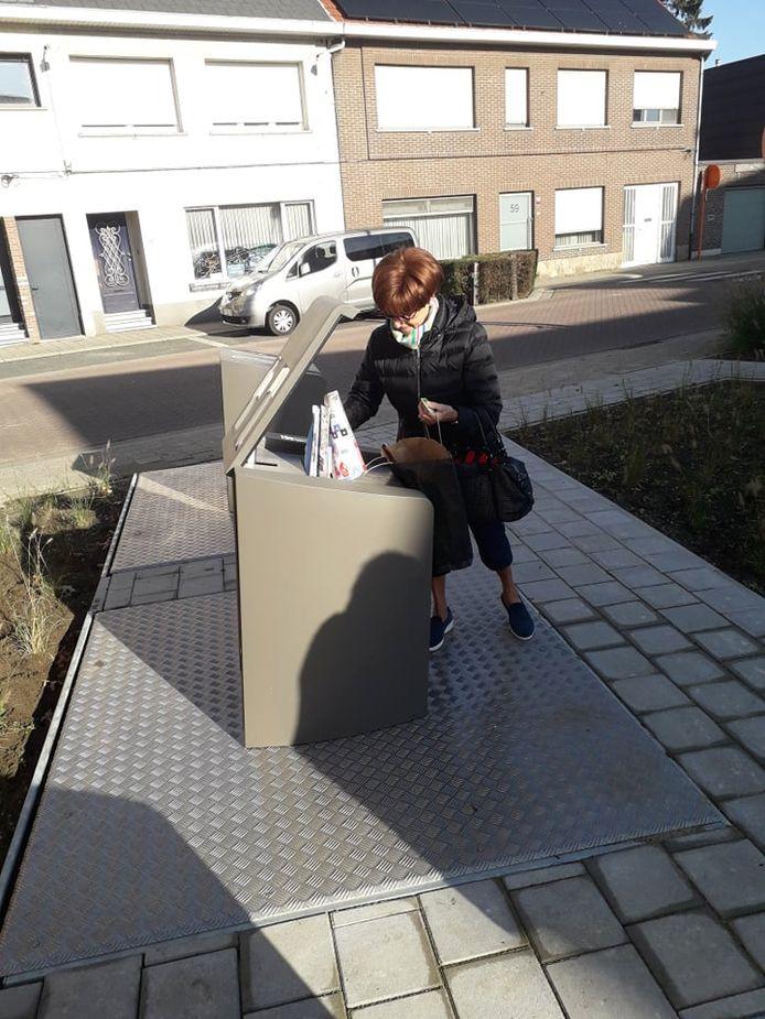 Een bewoonster dropt afval in de container.