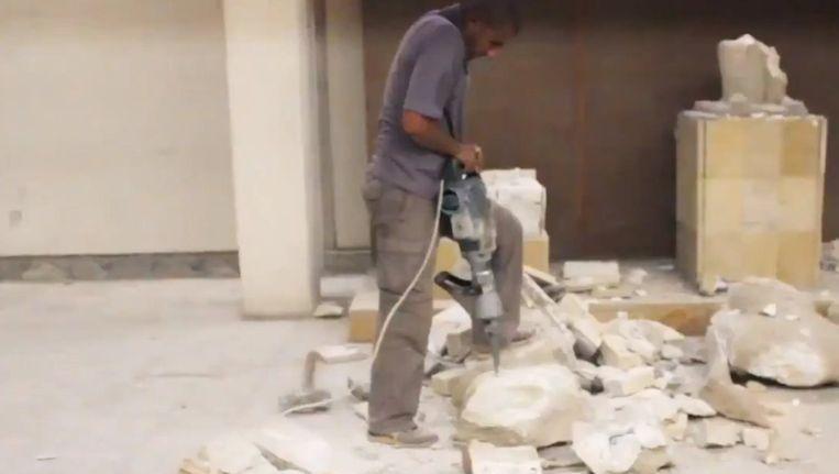Een IS-militant gaat kunstwerken in het museum van Mosoel met een drilboor te lijf. Beeld PHOTO_NEWS