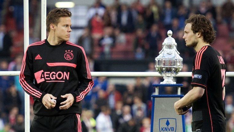 Niklas Moisander (L) en Daley Blind van Ajax lopen langs de beker na de verloren bekerfinale tegen PEC Zwolle. Beeld ANP