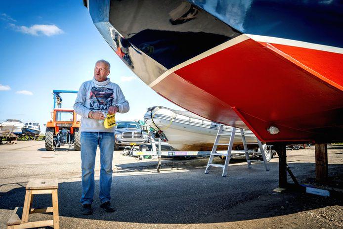 Henk van Berkel waxt zijn net geschilderde boot Dave. Morgen gaat hij het water in.