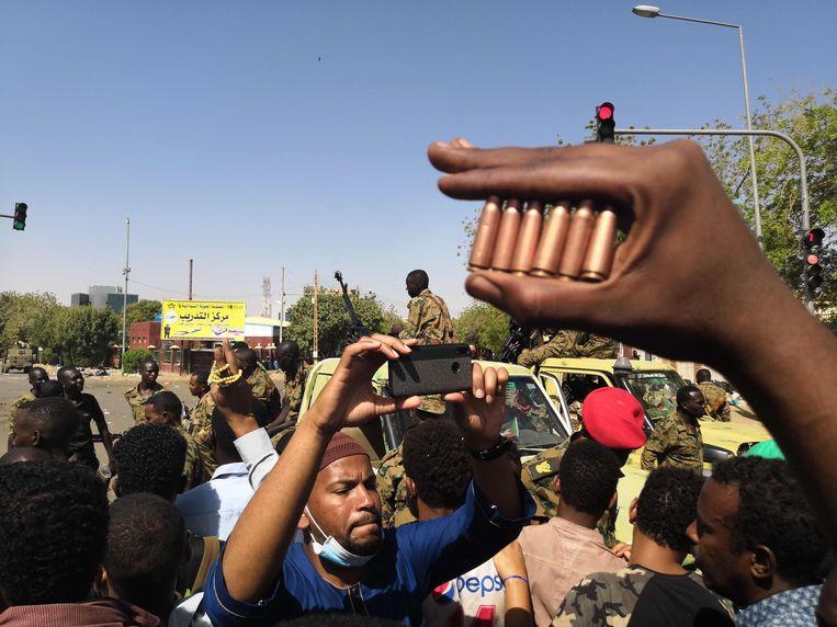 Een Sudanese demonstrant toont hulzen van kogels die door het leger zouden zijn afgeschoten tijdens een protest maandag in Khartoem. Beeld AFP