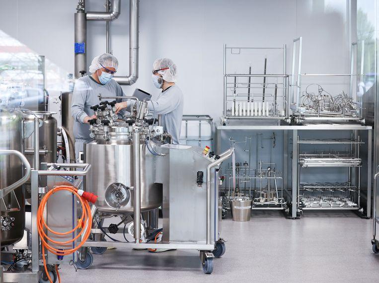 Werknemers van Allergopharma nabij Hamburg, Duitsland, bij de productie van het Pfizer/ BioNTech-vaccin. Wie beseft hoe baanbrekend de snelle ontwikkeling ervan is, vragen de auteurs zich af.  Beeld via REUTERS