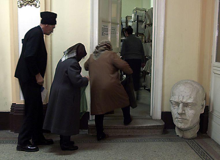 Kiezers in 2002 in een stembureau in de Roemeense stad Cluj passeren een beeld van Ion Antonescu. (Reuters) Beeld Reuters