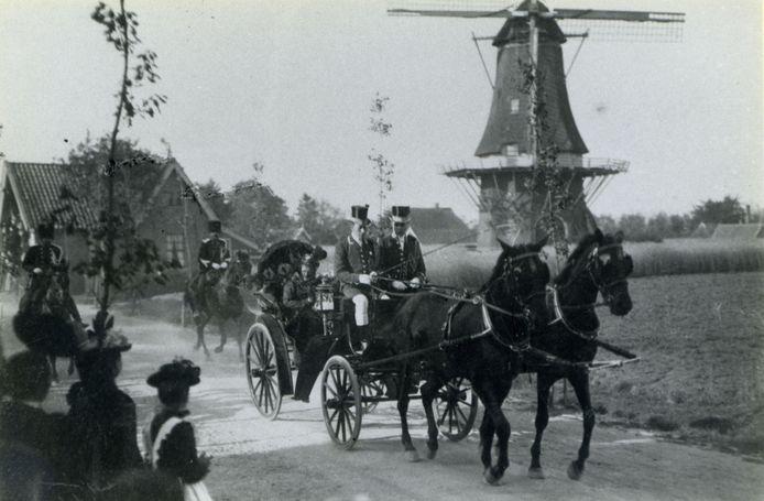 De koets met prinses Emma rijdt in 1902 langs korenmolen De Hoop in Hellendoorn. De bevolking uit het dorp is uitgelopen om deze koninklijke hoogheid te zien.