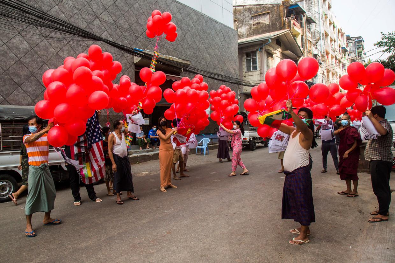 Demonstranten tegen de militaire coup houden ballonnen omhoog in de stad Yangon. Beeld AP
