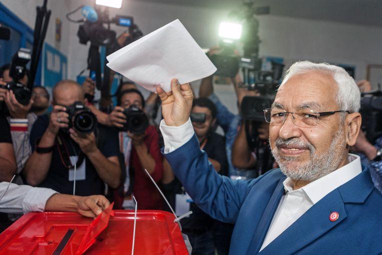 Rachid Ghannouchi, de leider van de partij Ennahda, laat zijn stembiljet zien voordat hij het inlevert. Beeld null