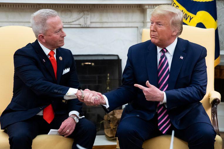 Jeff Van Drew (links) schudt de hand van president Donald Trump tijdens een persmoment in het Witte Huis. Beeld EPA