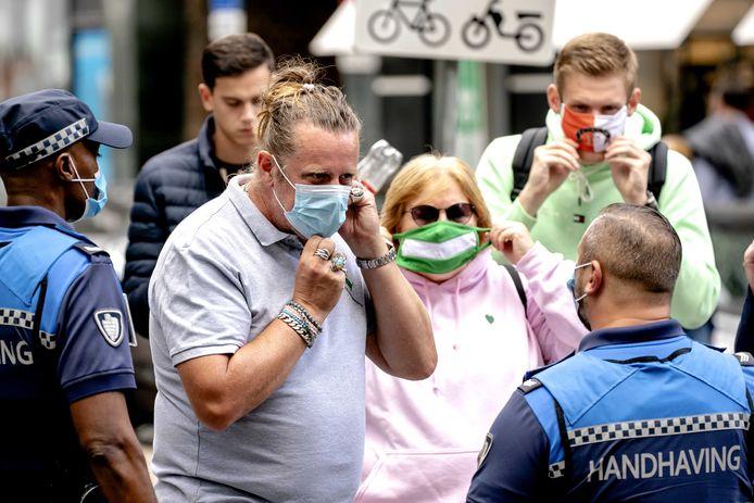 ROTTERDAM - Stadsgids en Rotterdamambassadeur Willem van Wijk in gesprek met een bevriende handhaver. De gids bespreekt de maatregelen rond het dragen van mondkapjes, die ook gaan gelden voor de toeristen die hij rondleidt.