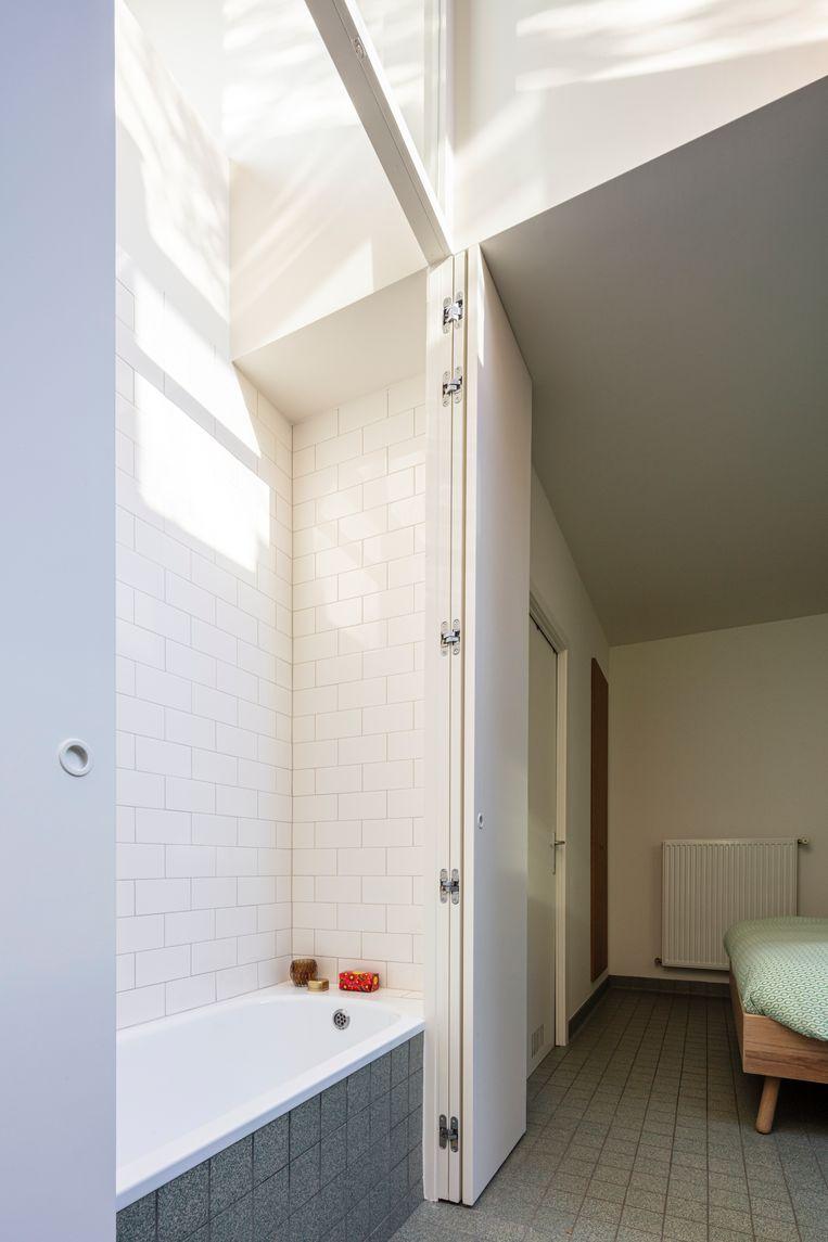 Zowel het ligbad als de douche zitten verstopt achter een kastdeur in de doorgang van de living naar de ouderslaapkamer.   Beeld Tim van de Velde