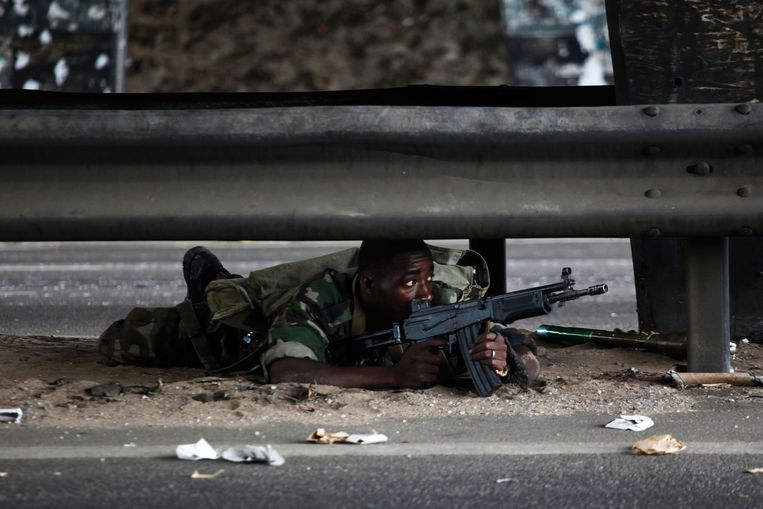 A soldier loyal to Ivory Coast presidential claimant Alassane Ouattara lies on a road as fighting flares across the country's main city Abidjan April 4, 2011. U.N. and French helicopters attacked Laurent Gbagbo's last strongholds in Abidjan on Monday as forces loyal to Ouattara streamed into the city from the north.  REUTERS/Emmanuel Braun (IVORY COAST - Tags: POLITICS CIVIL UNREST IMAGES OF THE DAY) Beeld REUTERS