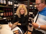 Bonnie St. Claire signeert in Eindhoven tussen de flessen drank
