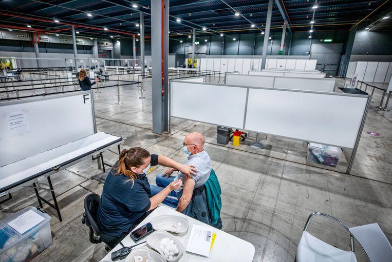 Een man wordt in het voorjaar van dit jaar in Utrecht gevaccineerd. In theorie wordt groepsimmuniteit bereikt (de situatie waarbij het virus helemaal niet meer rondgaat) als zo'n 85 procent van de gehele bevolking beschermd is tegen het virus, door vaccinatie of eerdere besmetting.  Beeld Raymond Rutting / de Volkskrant