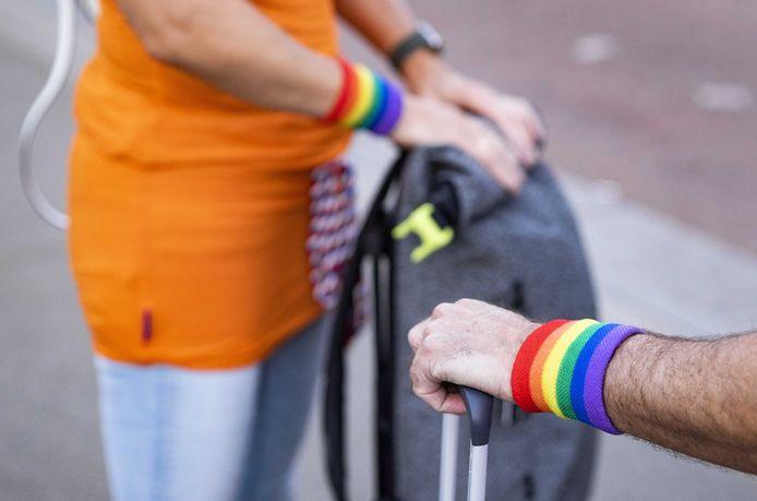 Presentator Klaas van Kruistum overhandigt een voetbalfan een regenboogvlag op Schiphol.