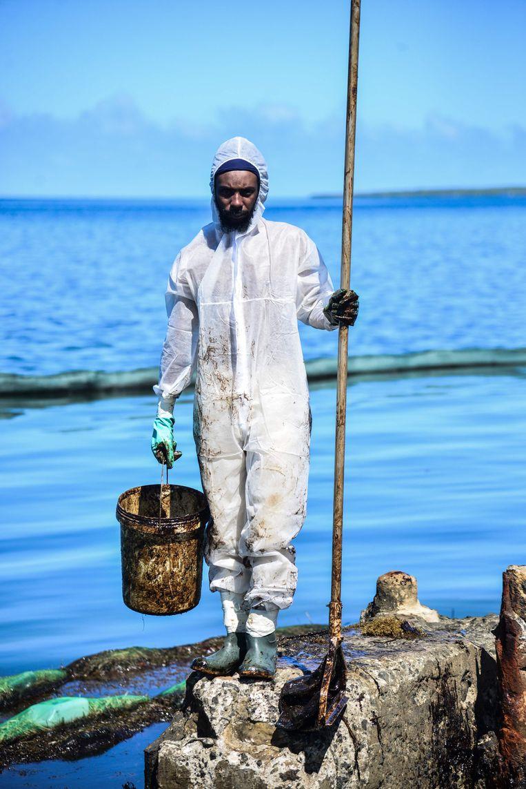 Een vrijwilliger zeult met een emmer olie, gelekt uit de Japanse olietanker MVWakashio.Het schip strandde voor de kust van Bois des Amourettes, Mauritius. Beeld AFP