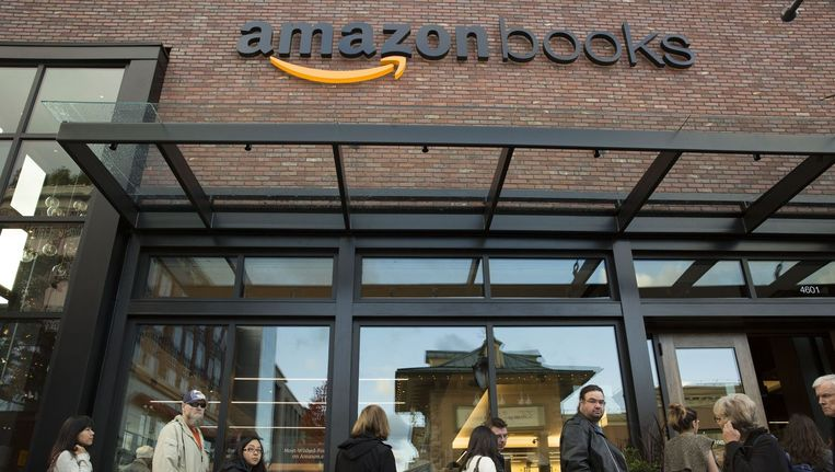 Klanten staan in de rij voor de opening van Amazons eerste fysieke winkel. Beeld afp