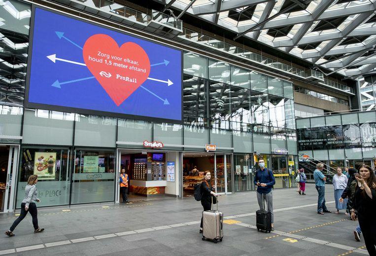 Een oproep om 1,5 meter afstand te houden op Den Haag Centraal Station. Ruim een kwart van de reizigers klaagt erover dat medereizigers geen mondkapje dragen of dat op een onjuiste manier doen, zegt reizigersvereniging Rover.  Beeld ANP