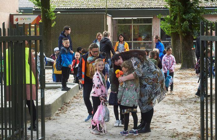 Kinderen van de door brand beschadigde basisschool John F. Kennedy in Oss komen voor het eerst bij De Korenaer. De juffen vangen hen op het plein op.