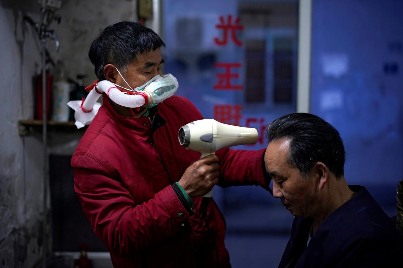 Een kapper in Wuhan is weer aan het werk nu de lockdown is opgeheven. Beeld REUTERS