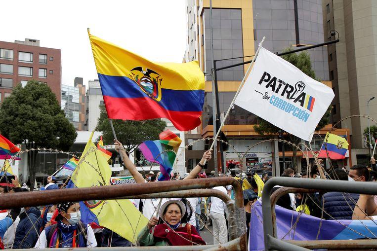 Aanhangers van de presidentskandidaten Yaku Perez en Guillermo Lasso verzamelen zich voor het kantoor van de Nationale Kiesraad van Ecuador in de hoofdstad Quito. Beeld REUTERS