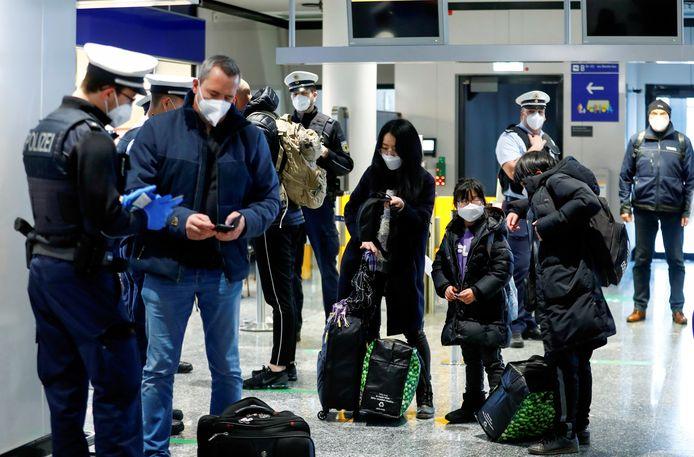 Agenten controleren reizigers uit het Verenigd Koninkrijk op de luchthaven van Frankfurt.