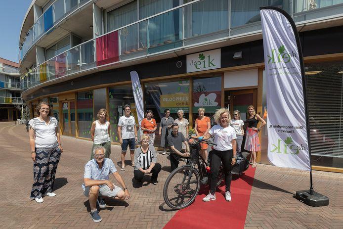 Evelien van der Werff (bij de fiets) fietst door heel Nederland langs alle inloophuizen en hier wordt ze verwelkomd in inloophuis De Eik.